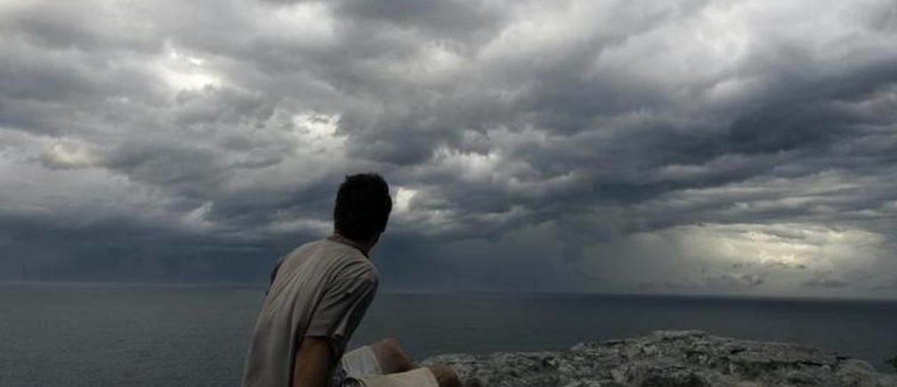 A man watches seasonal autumn storm clouds gather over the sea ahead of steady rain off the coast of Sydney March 8, 2007. Many parts of Australia are in the grip of the worst drought in 100 years, forcing authorities to impose water restrictions exacerbated when rainfall misses catchment areas. REUTERS/Will Burgess      (AUSTRALIA)