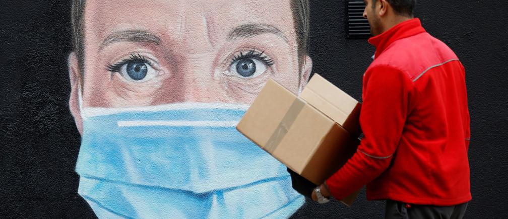 Un trabajador postal camina junto a un mural de un trabajador del NHS en una ventana del centro de la ciudad de Manchester, tras el brote de la enfermedad coronavirus (COVID-19), Manchester, Gran Bretaña, 18 de mayo de 2020.
