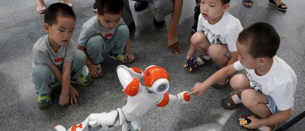A boy touches a robot as it performs Taiji, a traditional form of Chinese martial arts, at the World Robot Conference (WRC) in Beijing, China August 17, 2018. REUTERS/Jason Lee - RC16E1FE94F0