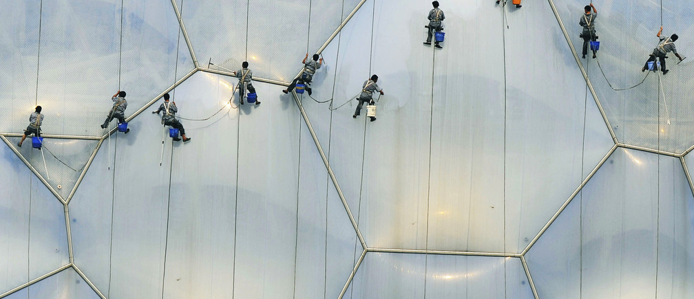 Workers clean the exterior of the National Aquatics Center, also known as the Water Cube, at the Olympic Green in Beijing, July 18, 2008. With less than a month to go to the Olympics, Beijing and neighbouring provinces have asked polluting industries to shut or reduce production to clean the air for athletes, and to help offset a looming power shortage. REUTERS/Ge Gong (CHINA) (BEIJING OLYMPICS 2008 PREVIEW) - GM1E47I1ED301