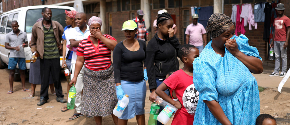 Residents of Madala Men's Hostel cover their noses as they stand in a queue waiting to collect sanitiser from health workers during a nationwide lockdown for 21 days to try to contain the coronavirus disease (COVID-19) outbreak, in Alexandra, South Africa  April 1, 2020. REUTERS/Siphiwe Sibeko - RC2QVF9CAZ09