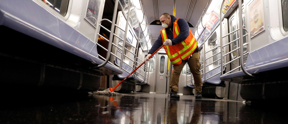 A worker mops the floor as the MTA Subway closed overnight for cleaning and disinfecting during the outbreak of the coronavirus disease (COVID-19) in the Brooklyn borough of New York City, U.S., May 7, 2020. REUTERS/Andrew Kelly - RC2IJG954J5Q