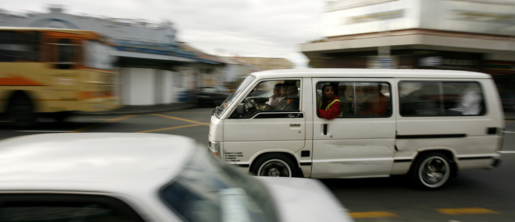 Minibus taxis ferry passengers in Cape Town August 15, 2007. Armed with pistols and fiery tempers, South Africa's minibus taxi drivers are the undisputed kings of road rage, cutting people off and flying through redlights as nervous motorists clear the way. To match feature SAFRICA-TAXIS/   REUTERS/Mike Hutchings (SOUTH AFRICA) - PM1DVYCUZKAA