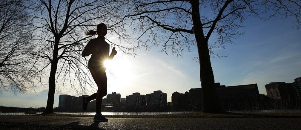 A woman jogs along the Charles River on an early spring evening in Boston, Massachusetts April 3, 2014.