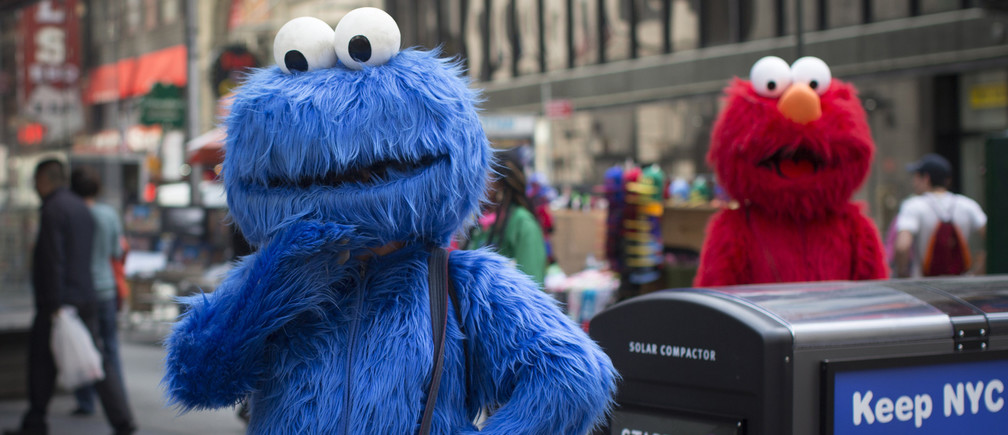 Characters dressed up as the Cookie Monster and Elmo from Sesame Street stand in Times Square while waiting to pose for photographs with people for tips in New York April 9, 2013. REUTERS/Shannon Stapleton (UNITED STATES - Tags: SOCIETY) - GM1E94A08RI01