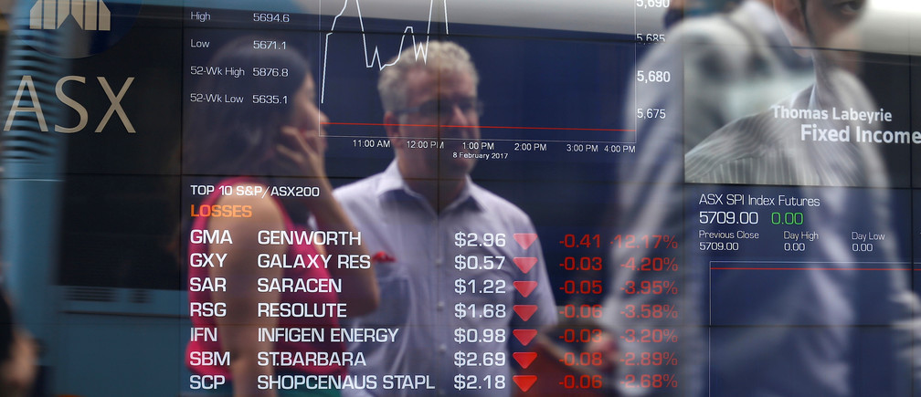 Investors are reflected in a window as they talk in front of a board displaying stock prices at the Australian Securities Exchange (ASX) in Sydney, Australia, February 8, 2017. REUTERS/Steven Saphore - RTX3030U