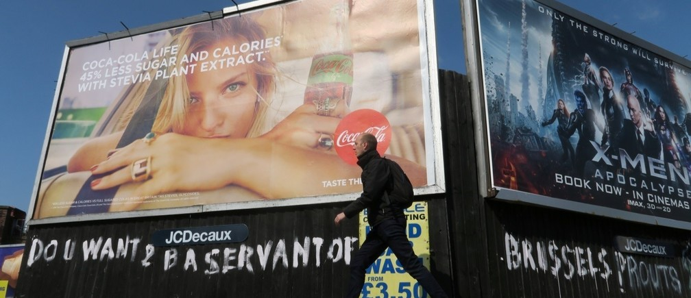 A man walks past BREXIT related graffiti that reads 'do U want 2 B a servant of Brussels' in Leamington Spa, Britain