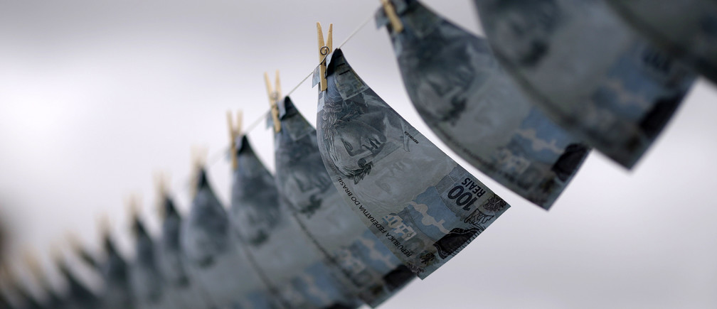 Replicas of R$100,00 banknotes are hung on a clothesline during a protest of the national union of prosecutors against money laundering in Brazil, at the Esplanade of Ministries in Brasilia March 18, 2015. REUTERS/Ueslei Marcelino (BRAZIL - Tags: POLITICS CIVIL UNREST TPX IMAGES OF THE DAY) - GM1EB3J00SV01