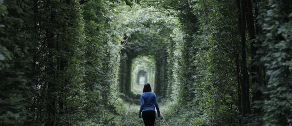 "A girl walks on a disused railway track, through what is known locally as the ""Tunnel of Love"", in small town Kleven some 350km (217 miles) off western Kiev May 13, 2012. REUTERS/Gleb Granich (UKRAINE - Tags: SOCIETY)"