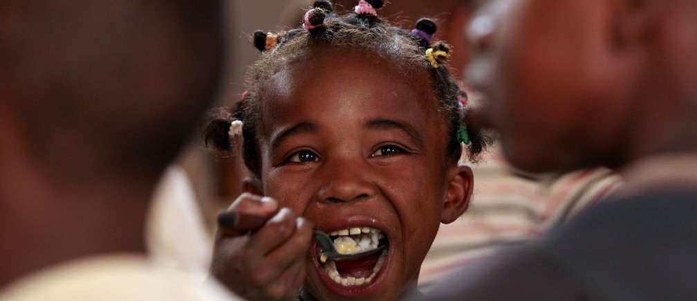 A Malagasy child eats at the United Nations World Food Program (WFP) school feeding initiative at the Saint de Paul community centre in Tanjombato, a southern suburb of the capital Antananarivo, October 28, 2013.