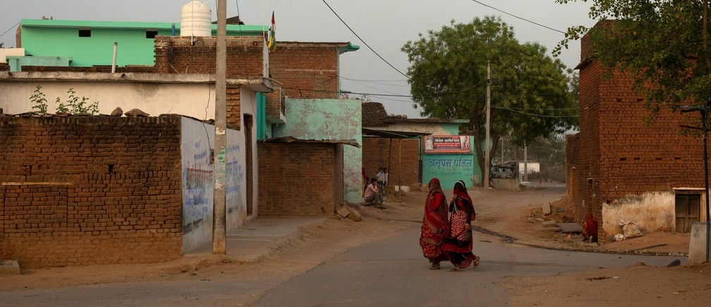 Women walk through an empty street during nationwide lockdown in India to slow the spread of the coronavirus, in Jugyai village in the central state of Madhya Pradesh, India, April 8, 2020.