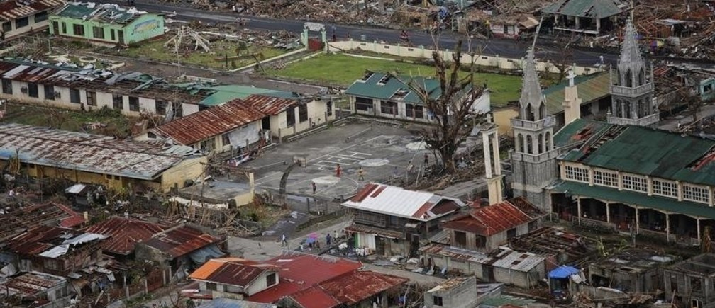 A coastal town destroyed by Typhoon Haiyan is seen from a military helicopter delivering aid north of Tacloban November 17, 2013. Mobbed by hungry villagers, U.S. military helicopters dropped desperately needed aid into remote areas of the typhoon-ravaged central Philippines, as survivors of the disaster flocked to ruined churches on Sunday to pray for their uncertain future. The Philippines is facing up to an enormous rebuilding task from Typhoon Haiyan, which killed at least 3,681 people and left 1,186 missing, with many isolated communities yet to receive significant aid despite a massive international relief effort.