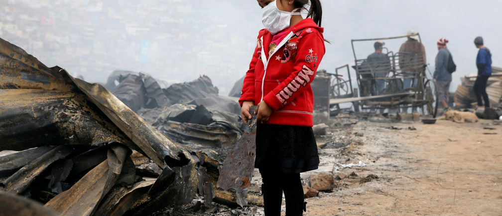 A child stands at the scene of a fire at 'Cantagallo' shanty town in Rimac district of Lima, Peru November 4, 2016. REUTERS/Guadalupe Pardo - RTX2RXYR