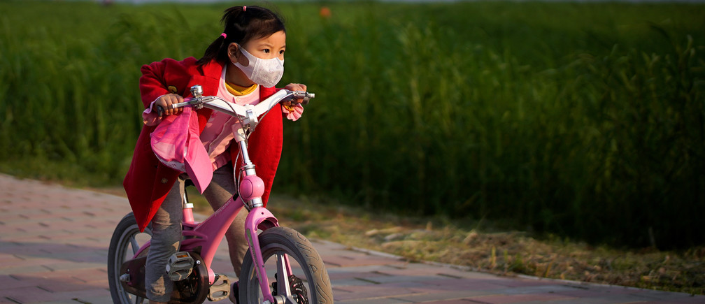 A girl wearing a face mask rides her bicycle  at a park after the lockdown was lifted in Wuhan, capital of Hubei province and China's epicentre of the novel coronavirus disease (COVID-19) outbreak, April 12, 2020. REUTERS/Aly Song - RC223G9M7R84