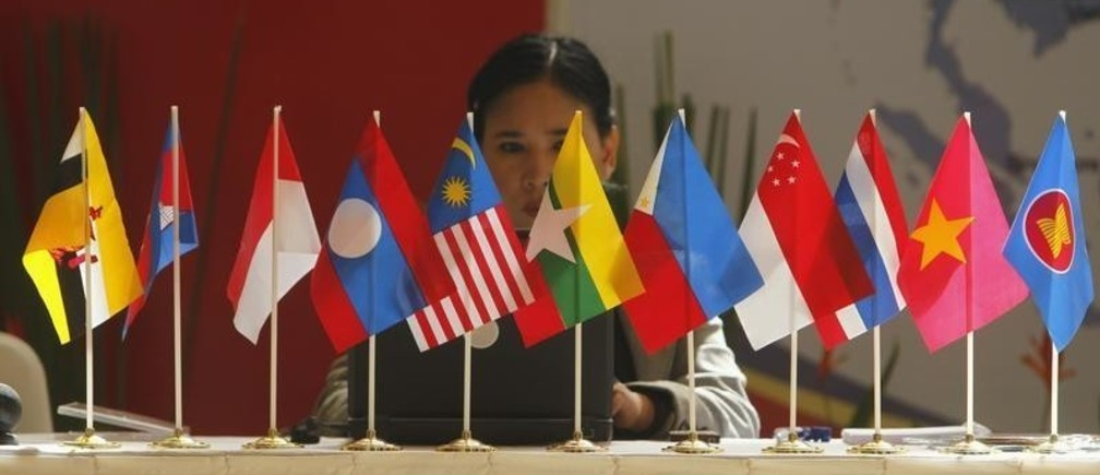 A woman sits in front of flags of the Association of South East Asian Nations (ASEAN) at Bali Nusa Dua Convention Centre in Bali November 16, 2011. Bali is hosting this year's ASEAN summit.   REUTERS/Beawiharta (INDONESIA - Tags: POLITICS) - GM1E7BG0T4201