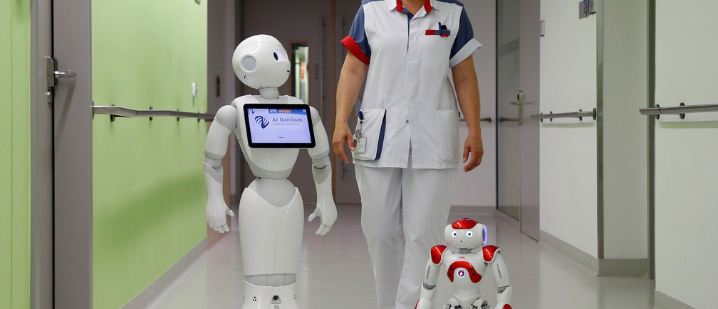 "A nurse walks with ""Pepper"" (L) and ""Zora"" the robots, humanoid robots designed to welcome and take care of visitors and patients, at AZ Damiaan hospital in Ostend, Belgium June 16, 2016. REUTERS/Francois Lenoir - D1AETKGAYXAA"