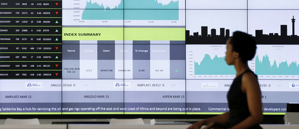 A worker walks past an electronic board displaying movements in major indices, at the Johannesburg Stock Exchange in Sandton, February 12, 2015. South Africa's rand weakened in early trade on Thursday ahead of President Jacob Zuma's annual state of the nation address, which investors hope would tackle domestic economic woes including electricity shortage.At 0704 GMT the rand was trading 0.22 percent softer at 11.8615 to the dollar, compared to its closing level of 11.8350 on Wednesday. REUTERS/Siphiwe Sibeko (SOUTH AFRICA - Tags: BUSINESS) - GM1EB2C1PH401