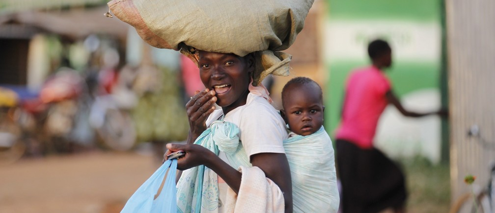 A woman carries a child and a bag on her head within the trading centre of the U.S. President Barack Obama's ancestral village of Nyang'oma Kogelo, west of Kenya's capital Nairobi, July 15, 2015.