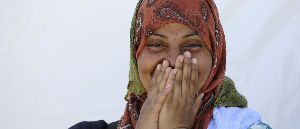 A migrant woman from Somalia smiles at a transit camp in Gevgelija, Macedonia, after entering the country by crossing the border with Greece, September 12, 2015. Macedonia is considering building a Hungarian-style border fence to stem a rising influx of migrants from the south, Foreign Minister Nikola Poposki was quoted as saying on Thursday. REUTERS/Ognen Teofilovski - RTSQUE