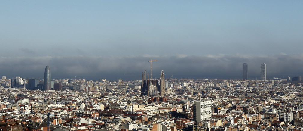 The Basilica Sagrada Familia (C) is seen as fog gradually recedes in Barcelona March 16, 2012. The condition was caused by a great difference in the temperature between the sea and the air, according to local media. REUTERS/Albert Gea (SPAIN - Tags: CITYSPACE ENVIRONMENT) - RTR2ZGJP