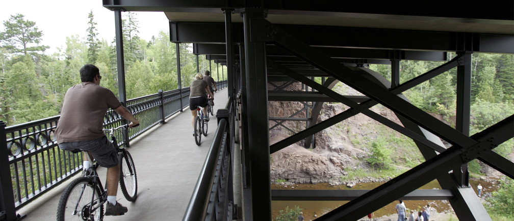 Cyclists ride on a pedestrian section below the bridge that spans the Gooseberry River, north of Duluth, Minnesota, August 5, 2007. The deck truss bridge is one of at least six that the Minnesota Department of Transportation is inspecting in wake of the collapse of the Interstate 35W bridge over the Mississippi River, August 1.   REUTERS/Eric Miller (UNITED STATES) - GF1DVWDAIRAA