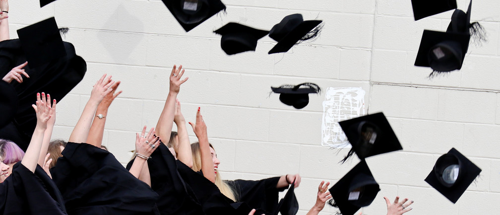 Warwick University graduates throw their graduation mortar boards into the air in celebration on the day of their graduation ceremony in Warwick, Britain July 17, 2017. Picture taken July 17, 2017.      REUTERS/Russell Boyce - RTX3C37E