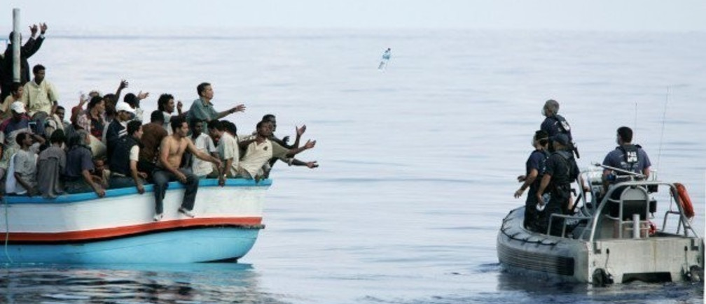 Armed Forces of Malta marines toss bottles of water to a group of around 180 illegal immigrants as a rescue operation gets underway after their vessel ran into engine trouble, some 30km (19 miles) southwest of Malta in this September 25, 2005 file photo. As many as 900 people may have died in Sunday's disaster off the coast of Libya. That would be the highest death toll in recent times among migrants, who are trafficked in the tens of thousands in rickety vessels across the Mediterranean. The mass deaths have caused shock in Europe, where a decision to scale back naval operations last year seems to have increased the risks for migrants without reducing their numbers. The European Union has proposed doubling the size of its Mediterranean search and rescue operations in response to the crisis. REUTERS/Darrin Zammit Lupi/Files MALTA OUT. NO COMMERCIAL OR EDITORIAL SALES IN MALTA TPX IMAGES OF THE DAY