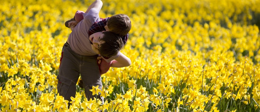 Children run through daffodils at St. James Park in London March 29, 2014.