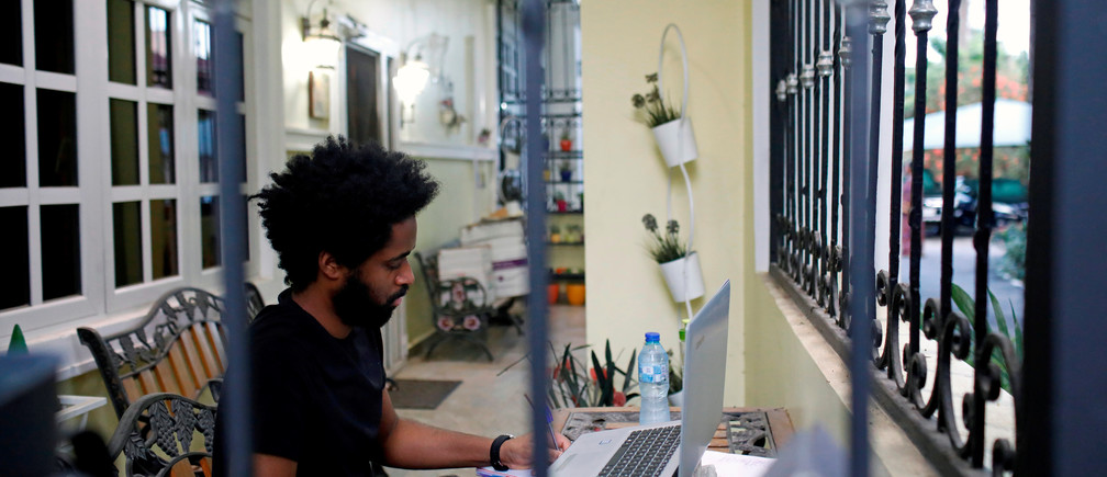 Alexander Caiafas, a 25 year-old data analyst, is seen working through a window into his home in Ikoyi, as authorities around the world impose various guidelines on lockdowns and social distancing to curb the spread of coronavirus disease (COVID-19), in Lagos, Nigeria May 25, 2020. When asked, what will you miss most about being in lockdown? Alexander replied: ' Spending quality time with relatives and parents because you know, thatÕs often hard to do. Secondly, I would say I miss speaking over the phone to close friends like on FaceTime, HouseParty, Zoom, all those kinds of applications'.  Picture taken May 25, 2020. REUTERS/Temilade Adelaja - RC2LXG98YSTW