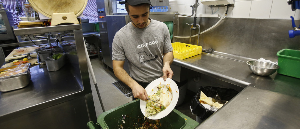A cook throws away leftovers in the 'Auf da Muehle' restaurant in the western Austrian village of Soell June 2, 2013. Andreas Koller, the owner of the restaurant, says only about 5-10 percent of all food there is thrown away. The waste food is collected and sent weekly to a biogas plant, where it is used to help produce electricity. Cutting the amount of food that goes to waste is the special theme of this year's World Environment Day on June 5. The U.N. Food and Agriculture Organization estimates that about a third of all the food produced for human consumption worldwide every year is wasted. Picture taken June 2, 2013. REUTERS/Dominic Ebenbichler (AUSTRIA - Tags: ENVIRONMENT FOOD SOCIETY) - GM1E9650L7R01