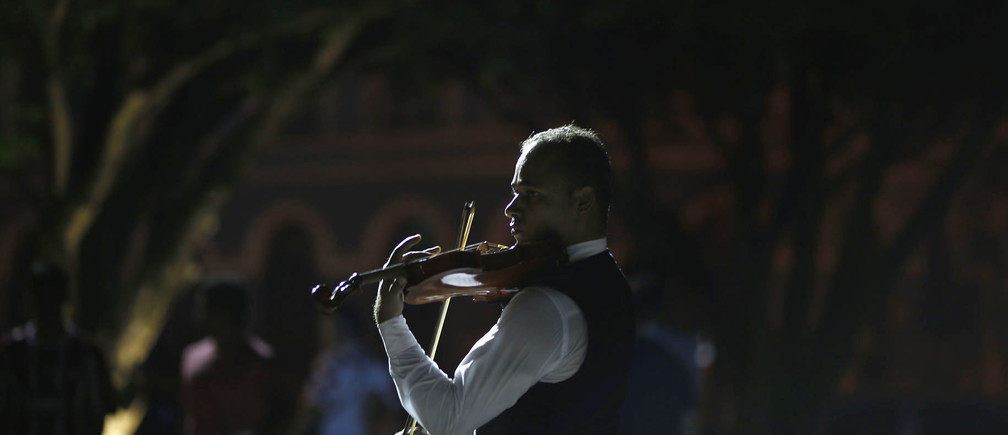 A man plays a violin for passersby during the 2014 World Cup, outside the Manaus Opera House June 16, 2014. In a project called 'On the Sidelines' Reuters photographers share pictures showing their own quirky and creative view of the 2014 World Cup in Brazil. REUTERS/Siphiwe Sibeko (BRAZIL - Tags: SPORT SOCCER WORLD CUP SOCIETY) - GM1EA6H0XLH01