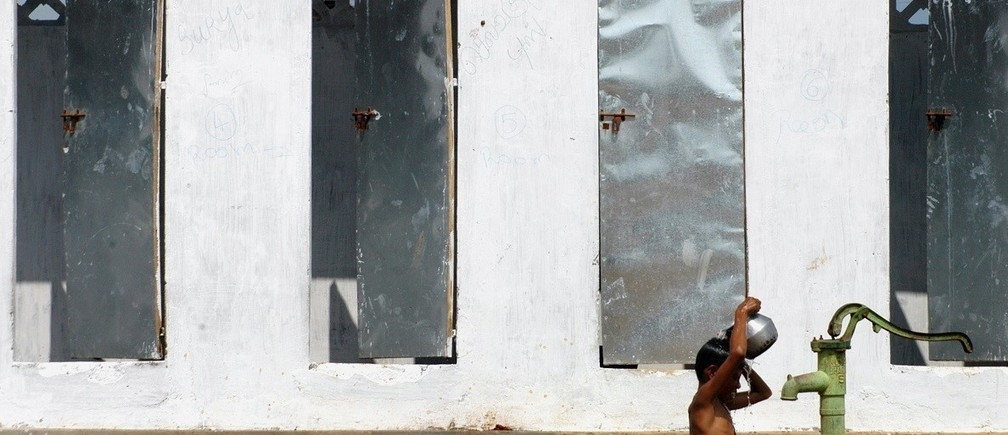 A boy takes bath outside newly built toilets in a village on the outskirts of Nagapattinam, about 325km (202 miles) from the southern Indian city of Chennai December 24, 2005. Government and multilateral agencies have pledged more than $7.3 billion in aid for nations hit by the December 26, 2004 earthquake and tsunami in the Indian Ocean, while global private donations amount to more than $5.7 billion. REUTERS/Jagadeesh NV - RTR1BITH