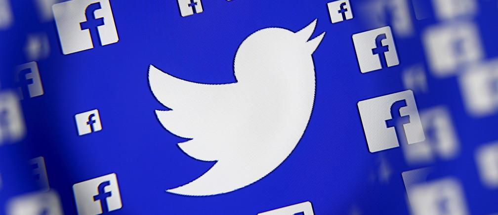 Logo of the Twitter and Facebook are seen through magnifier on display in this illustration taken in Sarajevo, Bosnia and Herzegovina, December 16, 2015. Broker's survey shows Twitter losing share to faster growing competitors such as Facebook's Instagram and Snapchat, despite co's multiple product and partnership launches this year, analysts write in note. REUTERS/Dado Ruvic - GF10000268362