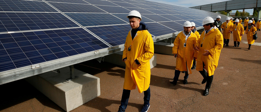 Visitors walk past solar panels at a solar power plant built on the site of the world's worst nuclear disaster, Chernobyl, Ukraine October 5, 2018. REUTERS/Gleb Garanich - RC113A3E7200