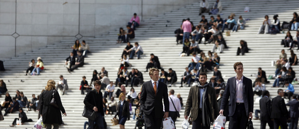 Businessmen and visitors enjoy the good weather on the stairs under the Arche de la Defense in the financial district of la Defense near Paris April 30, 2009