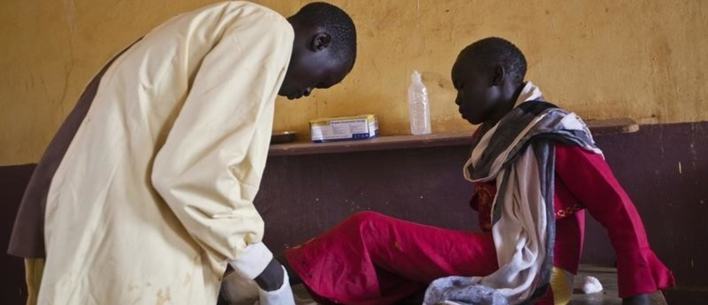 A girl is treated by a medic at the Aweil State Hospital in Aweil, the only hospital in the South Sudanese state of Northern Bahr el Ghazal, June 2, 2012. As in many developing nations, international aid is both an invaluable help to South Sudan and a crutch that sometimes enables it to avoid reality. Development experts have grown more sophisticated in recent decades about how they deliver aid. But in fragile states such as South Sudan, getting the balance right between helping a country and helping that country help itself remains incredibly difficult. Picture taken June 2, 2012.   To match Special Report SOUTH-SUDAN/AID  REUTERS/Adriane Ohanesian (SOUTH SUDAN - Tags: ANNIVERSARY HEALTH SOCIETY) - GM1E87A0K9L01