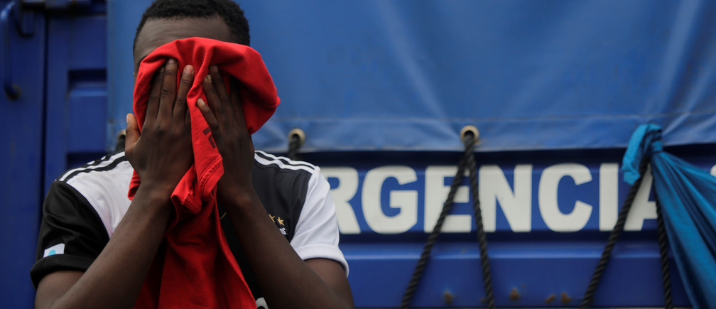 A migrant covers his face as African, Cuban and Haitian migrants, which are stranded in Honduras after borders were closed due to the coronavirus disease (COVID-19) outbreak, rest while trekking northward in an attempt to reach the United States, in Choluteca, Honduras June 2, 2020. REUTERS/Jorge Cabrera - RC291H9KN6S7