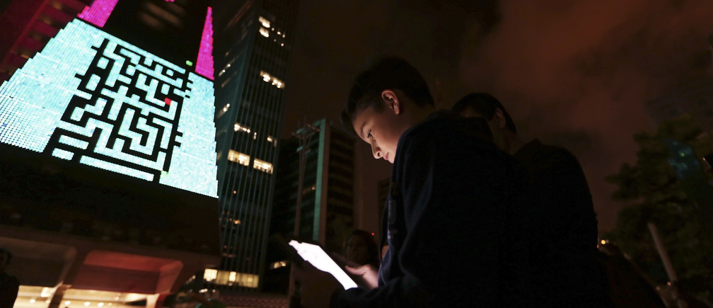 "A boy uses an iPad to play a video game, which is projected onto the surface of the Fiesp building, headquarters of the Industry Federation of Sao Paulo, during the ""Play!"" exhibition in the financial center of Sao Paulo's Avenida Paulista March 27, 2013."
