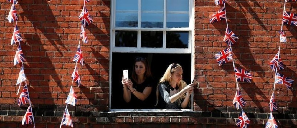 Women take photos on their smartphones as they lean out of the window of a building near Windsor Castle in Windsor, Britain, May 17, 2018. REUTERS/Damir Sagolj - RC1AD97D46F0