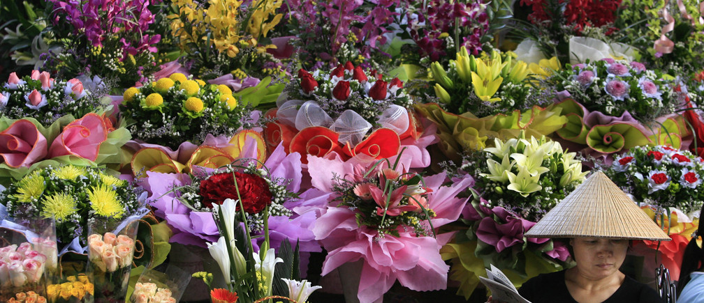 A woman reads a newspaper while selling flowers in a Hanoi market November 14, 2006.