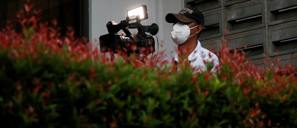A video journalist wearing a protective mask uses a camera at Halim Perdanakusuma airport, following the outbreak of the coronavirus in China, in Jakarta, Indonesia, February 15, 2020. REUTERS/Willy Kurniawan - RC2Y0F9V9OUI