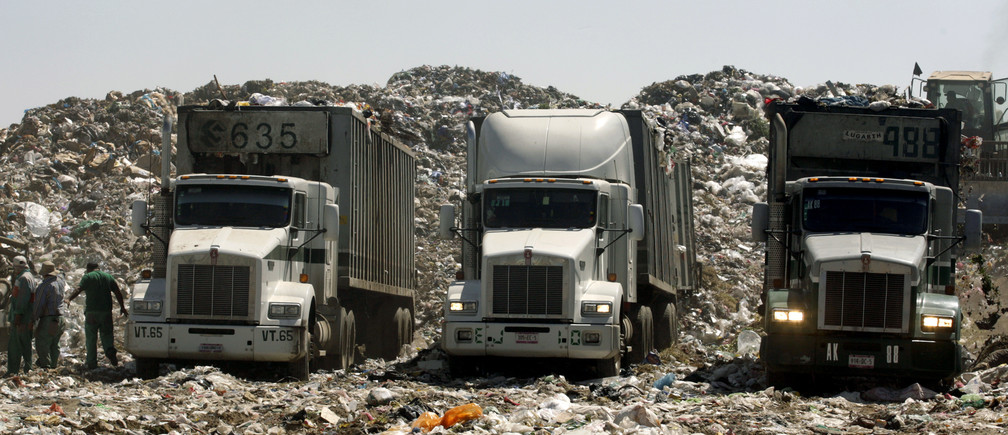 Trucks with garbage are parked at the Nezahualcoyotl dump site in Mexico City February 6, 2009. Mexico City is facing a crisis over where to put its trash -- enough to fill four sports stadiums a year -- with its sprawling dump already crammed to bursting and under a closure order. One of the world's biggest landfills, the Nezahualcoyotl dump site is a fifth the size of Manhattan and sits inside the urban sprawl of the fast-growing Mexican capital. Picture taken February 6, 2009.     REUTERS/Daniel Aguilar (MEXICO) - GM1E52D07FA01