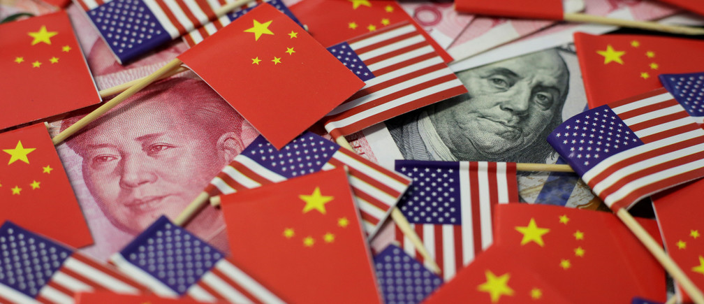 A U.S. dollar banknote featuring American founding father Benjamin Franklin and a China's yuan banknote featuring late Chinese chairman Mao Zedong are seen among U.S. and Chinese flags in this illustration picture taken May 20, 2019. Picture taken May 20, 2019. REUTERS/Jason Lee/Illustration - RC1964F35EE0
