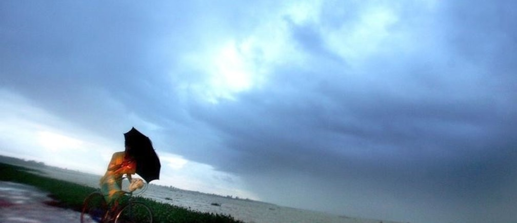 A Sri Lankan man holds an umbrella as he cycles past an overcast bay in the town of Kalmunai on Sri Lanka's east coast January 19, 2005. Sri Lanka upwardly revised its death toll figures on Monday, saying the December 26 tsunami killed at least 38,195 people along the country's south, easst and northern seaboard while more than 6,000 are still missing. Pictures of the month January 2005. Pictures of the Year 2005. NO RIGHTS CLEARANCES OR PERMISSIONS ARE REQUIRED FOR THIS IMAGE.  REUTERS/Arko Datta - RP5DRIHCNDAA