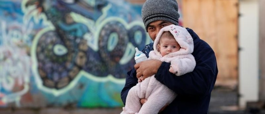 An afghan migrant and his baby are pictured in a camp for migrants in Grande-Synthe, France December 14, 2016. REUTERS/Pascal Rossignol - RTX2UYJB