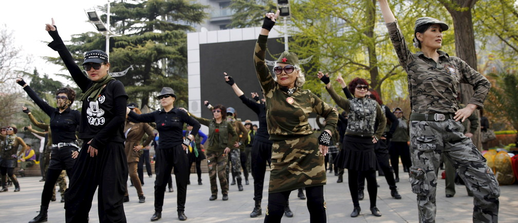Seventy-nine-year-old Wang Baorong (C), dressed in military style clothes, and other participants perform square dancing at a park square in Beijing, China, April 9, 2015. Chinese-style square dancing is running circles around other hobbies for the elderly, with millions taking to parks and plazas across China, swivelling their hips and rolling their arms - but it's not to everyone's liking. Picture taken on April 9, 2015. REUTERS/Kim Kyung-Hoon  - GF10000078735