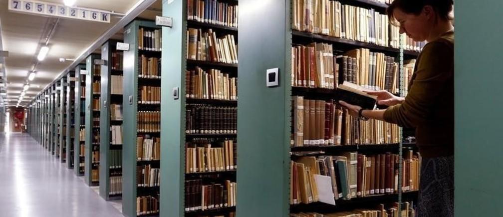 "A woman consults a book in the library of the university KU Leuven ""Katholieke Universiteit Leuven"" in Leuven, Belgium, June 8, 2016. REUTERS/Francois Lenoir - D1AETIXBFLAA"