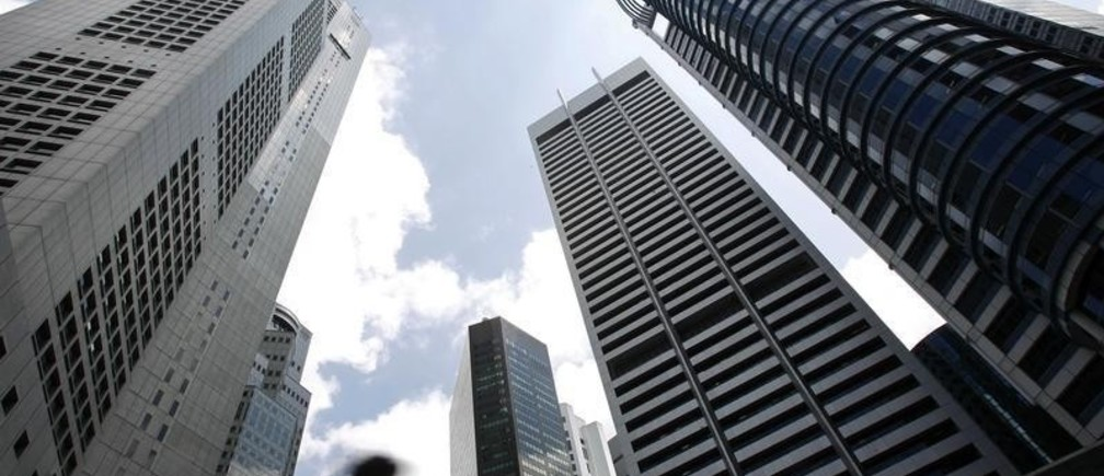 A man walks past buildings at the central business district of Singapore February 14, 2007. Singapore's trade-reliant economy expanded faster than expected in the fourth quarter on a pick up in domestic activity, data showed on Wednesday, prompting the government to lift its expectations for 2007.  REUTERS/Nicky Loh  (SINGAPORE) - RTR1MDL4