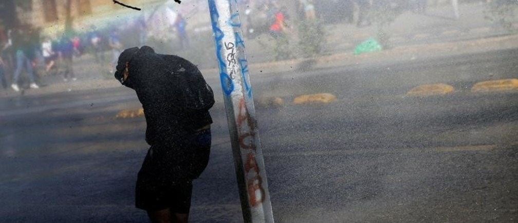 A demonstrator takes cover from tear gas and a water cannon during an anti-government protest in Santiago, Chile October 30, 2019. REUTERS/Edgard Garrido     TPX IMAGES OF THE DAY - RC1C25C43BD0