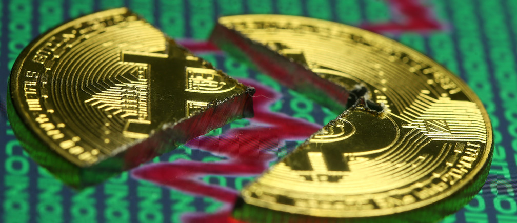 Broken representation of the Bitcoin virtual currency, placed on a monitor that displays stock graph and binary codes, are seen in this illustration picture, December 21, 2017. REUTERS/Dado Ruvic/Illustration - RC1F4FD1D3F0